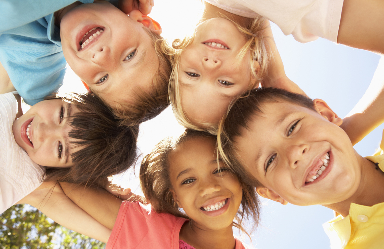 Group Of Children Looking Down Into Camera Smiling
